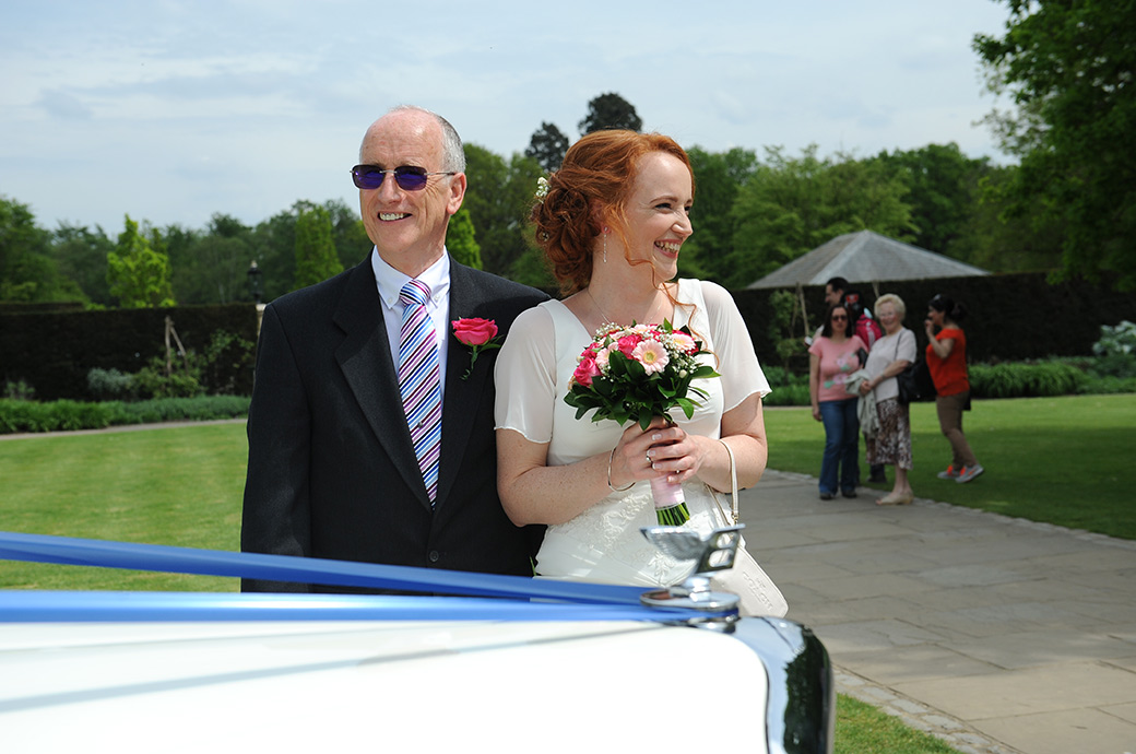 Wedding picture of an excited Bride at the entrance of Surrey wedding venue Pembroke Lodge as she stands with her smiling father by their classic white Bentley wedding car