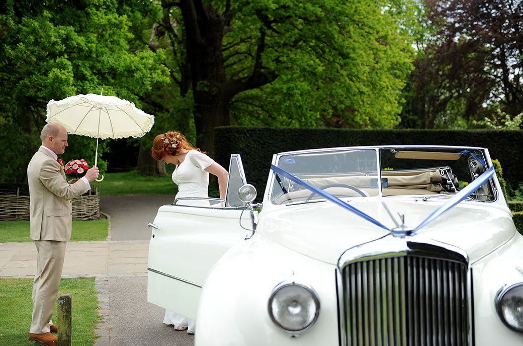 Groom captured in this wedding photo holding his Brides parasol and bouquet as she gets out of the white vintage convertible Bentley outside Pembroke Lodge in Richmond Park Surrey