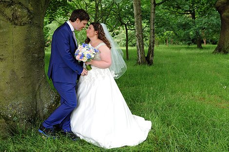 Newlyweds captured in this wedding photograph romantically standing together by a tree in the grass by the side of the Russell Suite at Pembroke Lodge in Richmond Surrey