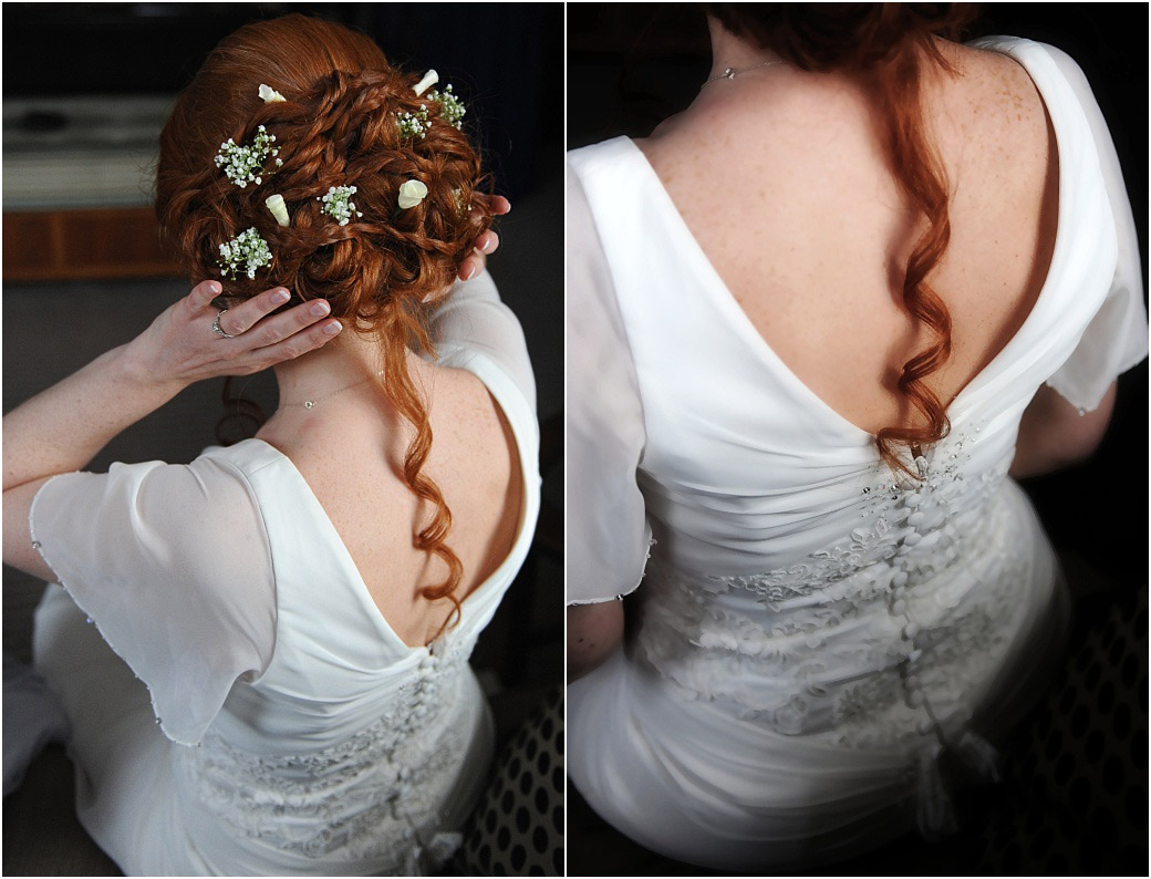 From behind view of the Bride in her wedding dress with her beautiful red hair full of delicate little flowers getting ready for Pembroke Lodge a great Surrey wedding venue
