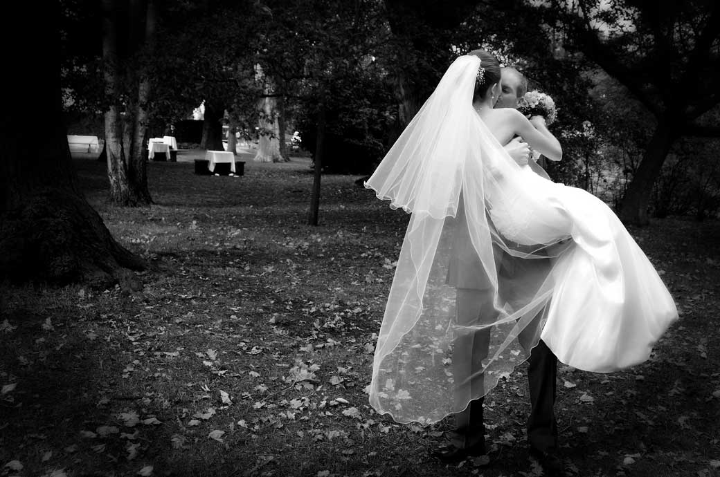 A beautifully romantic wedding photograph of the groom holding his bride up and kissing here outside the Russell Suite in Pembroke Lodge Richmond Park