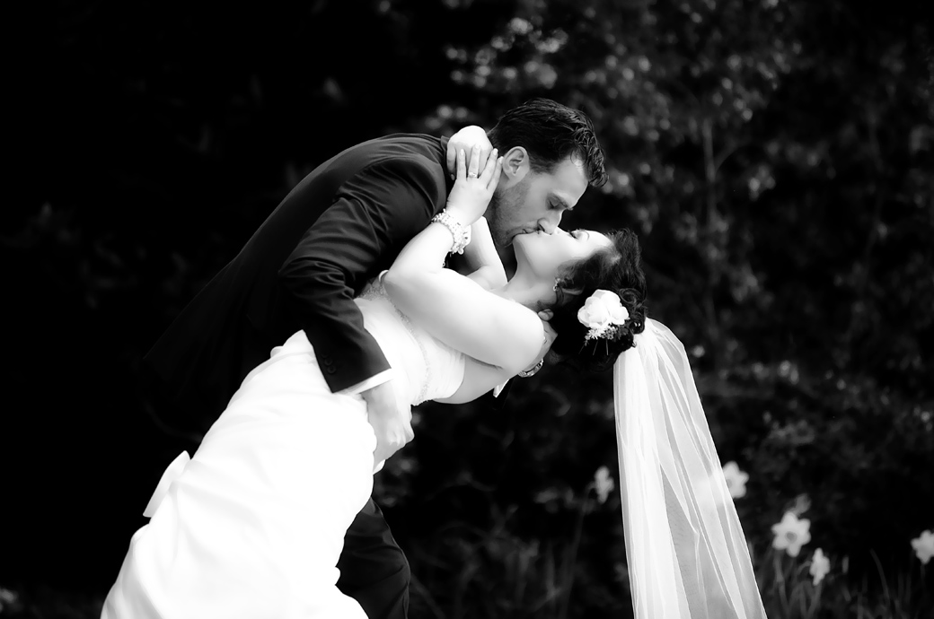 Bride swoons in the arms of her Groom as they pasionately kiss in this romantic and dramatic wedding photograph taken at Surrey wedding venue Pembroke Lodge in the woods