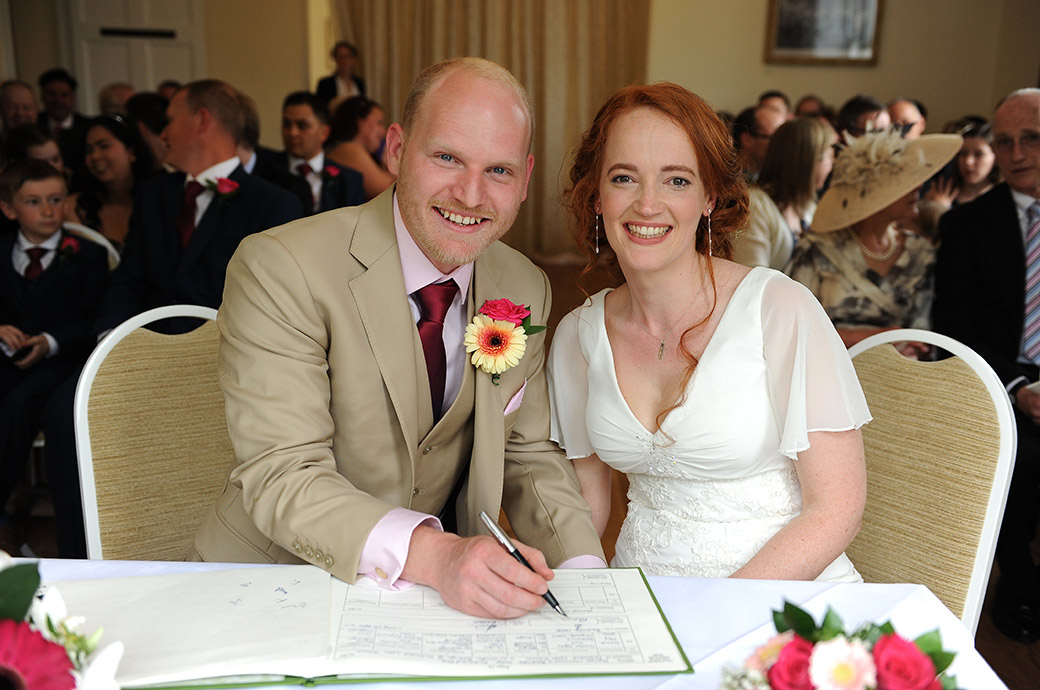 An excited beaming just married couple pose as they sign the marriage register in the Russell Suite at the ever popular Surrey wedding venue Pembroke Lodge in Richmond Park