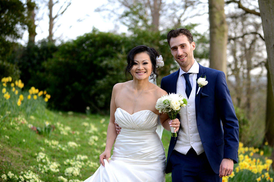 Smiling Bride and groom as they emerge from the bright flowers in this wedding photograph taken in the lovely woods surrounding Surrey wedding venue Pembroke Lodge
