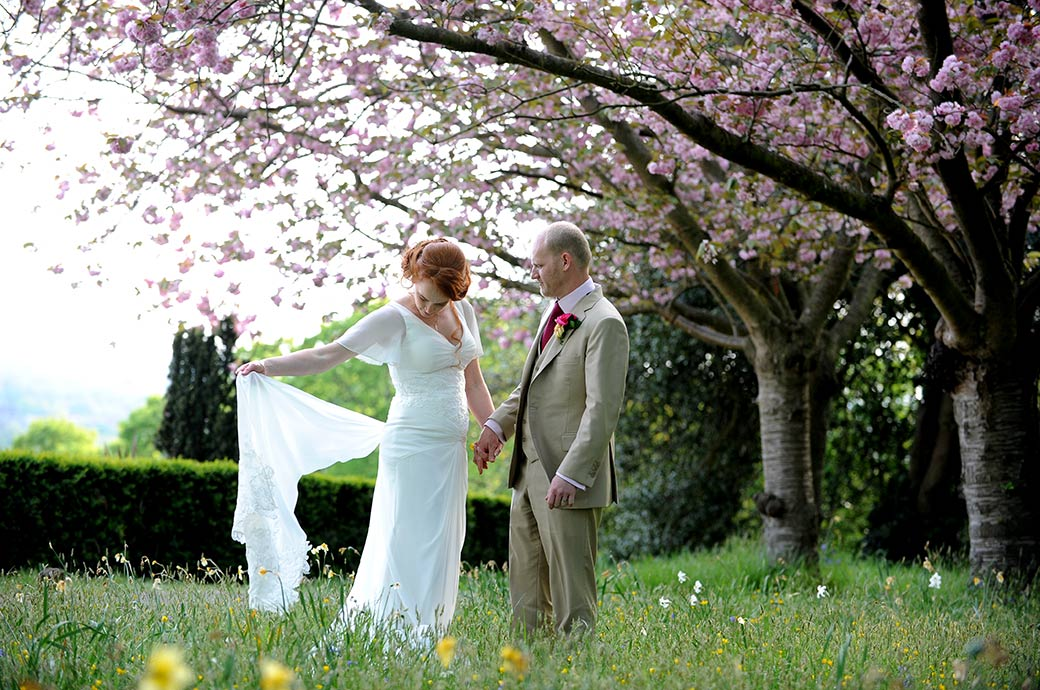 Beautiful wedding photograph of a Bride and groom at Surrey wedding venue Pembroke Lodge in Richmond Park standing in the long grass beneath the pink blossoming trees