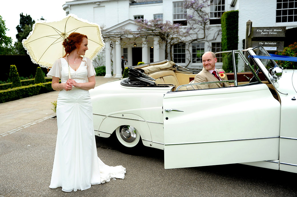 Wedding picture of a Bride with her white parasol outside Surrey wedding venue Pembroke Lodge looking over to the Groom sitting in a white vintage Bentley convertible