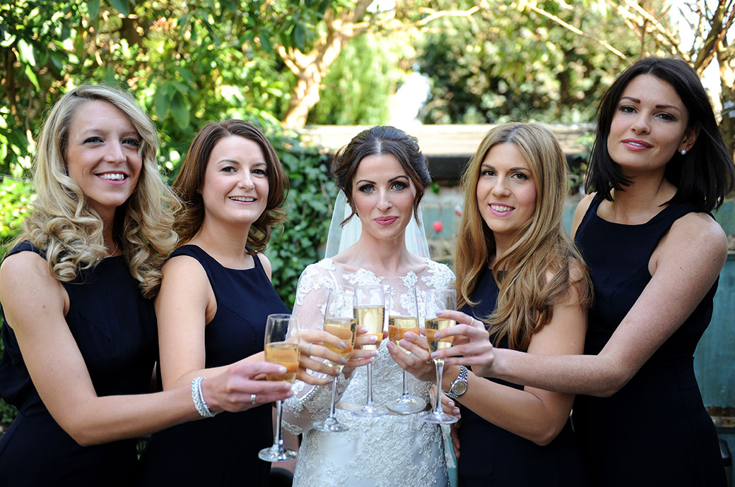 Informal wedding photograph of a Bride and her Bridesmaid all with champagne ready to leave for the Surrey church and wedding reception venue Pennyhill Park