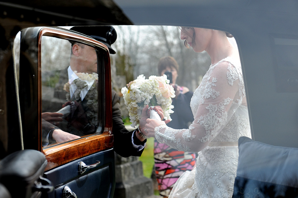 The Bride is helped with her wedding bouquet as she gets into the bridal car ready to leave for their Pennyhill Park drinks reception in Bagshot Surrey