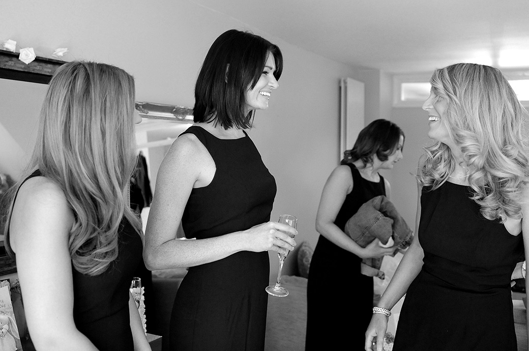 Smiling Bridesmaids enjoying the excitement and champagne on the morning of a wedding before the afternoon celebrations at the luxurious Surrey venue Pennyhill Park in Bagshot