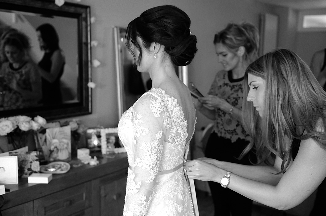 Bridesmaid buttoning up the Bride's wedding dress before her church marriage service and reception at Surrey wedding venue at the lovely Pennyhill Park hotel and Spa