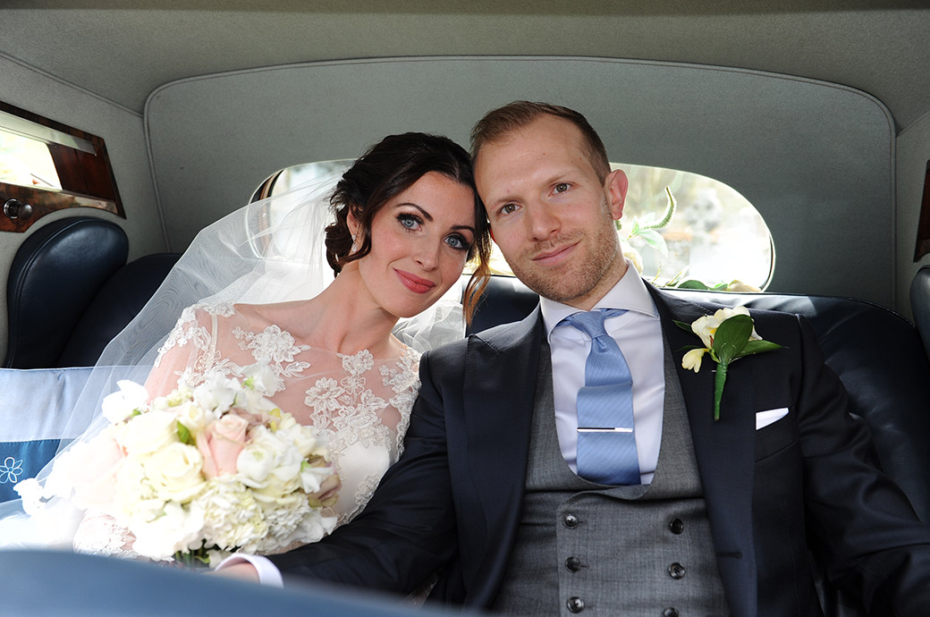 Loving couple looking radiant after their church marriage now in the bridal car ready for more celebrations at the exclusive and luxurious Surrey wedding venue Pennyhill Park