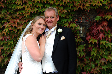 Happy content newlywed couple at the exclusive and luxurious Surrey wedding venue Pennyhill Park relax in front of a colourful ivy clad wall on their bridal suite balcony
