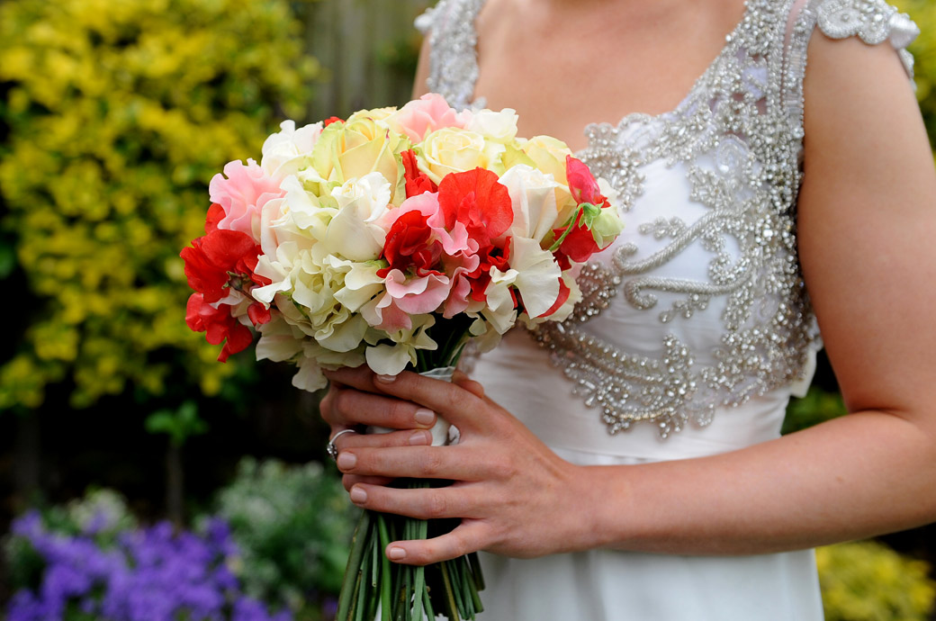 Bride's lovely colourful bouquet and beautifully detailed art deco style wedding dress captured in this wedding picture at Surrey wedding venue Ramster Hall in Chiddingfold, Guildford