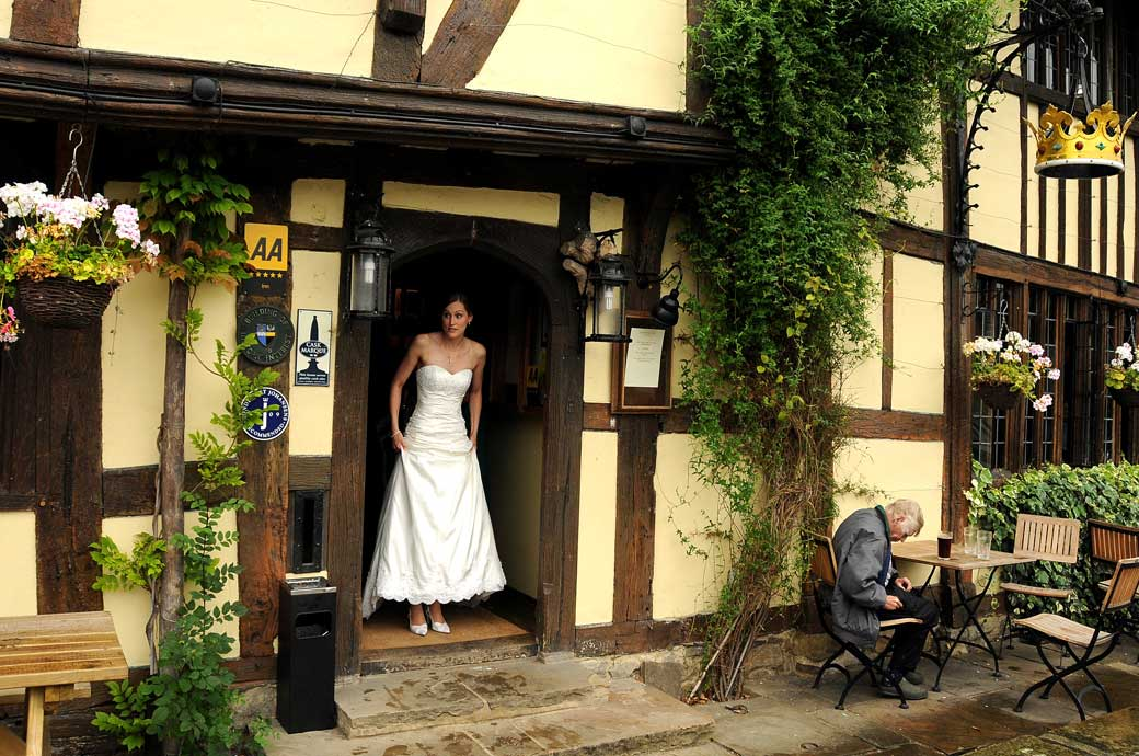 Beautiful Bride wedding photo watching the rain fall from the door of the Crown Pub Chiddingfold before leaving for Surrey wedding venue Ramster Hall