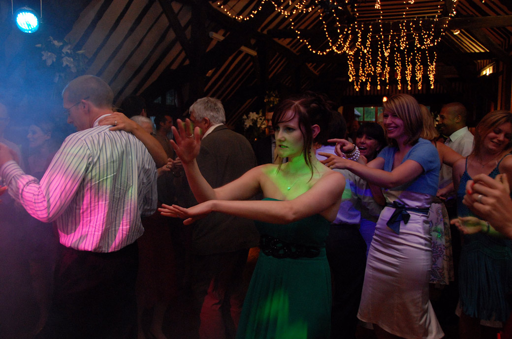 Intriguing ladies dance moves captured in the atmospherically lit Long Hall at Ramster Hall in Chiddingfold taken by a Surrey Lane wedding photographer