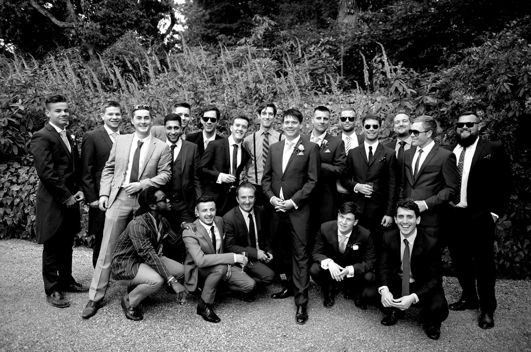 Happy and proud Groom strikes a pose with the gents for an informal wedding picture in the relaxing grounds at Ramster Hall in Chiddingfold a wedding venue in Surrey