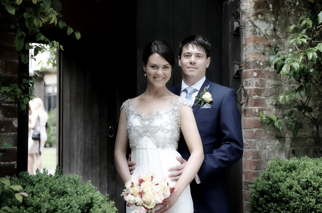 The beaming beautiful Bride held by her proud husband at Surrey wedding venue Ramster Hall in the entrance to The Courtyard Garden  and Long Hall