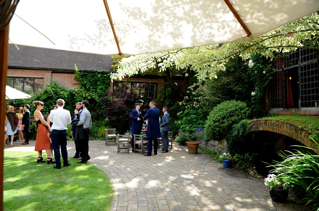 Distant wedding photo view from under a garden umbrella of guests relaxing over drinks in the beautiful and tranquil Courtyard Garden in Ramster Hall Surrey