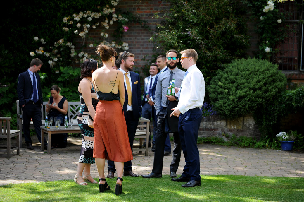 Wedding reception guests relax over drinks and engage in conversation in the lovely tranquil Courtyard Garden at Surrey wedding venue Ramster Hall in Chiddingfold village