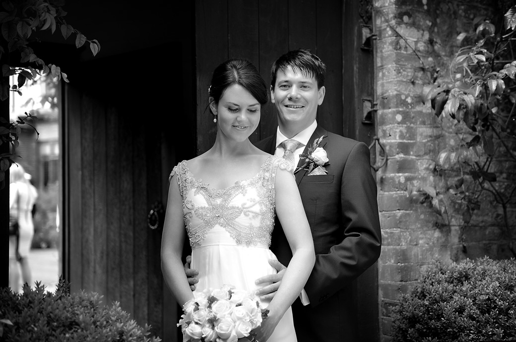 Happy smiling newlywed couple standing in the entrance to The Courtyard Garden at the enchanting and popular Ramster Hall in Chiddingfold Surrey
