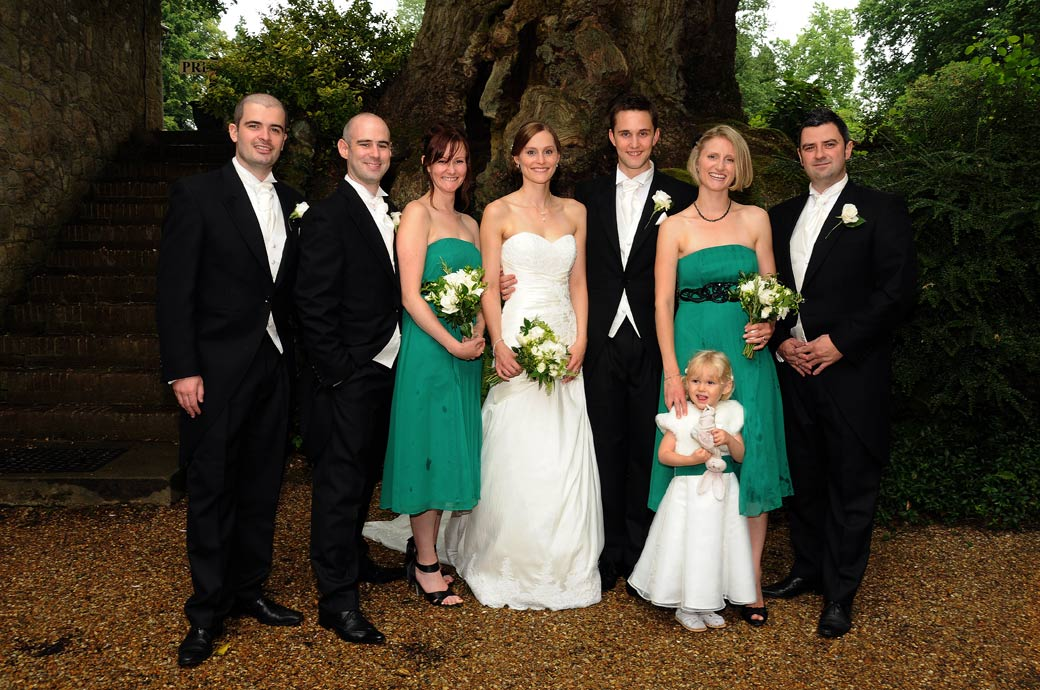 A happy group wedding picture of the wedding party all smiling under a tree out of the rain taken at Ramster Hall, a lovely wedding venue in Surrey