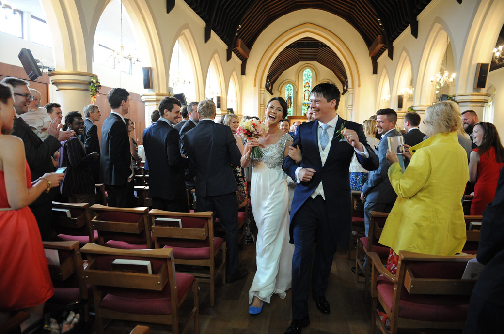 Joyful and exuberant couple enjoy walking down the aisle at Christ Church New Malden before leaving for Surrey wedding venue Ramster Hall in Chiddingfold for their reception