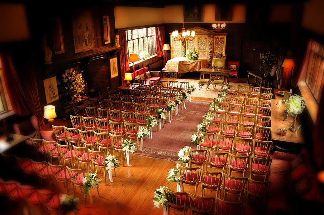 An atmospheric Great Drawing Room wedding photograph with pre-service empty seats taken from balcony at Surrey wedding venue Ramster Hall, Guildford