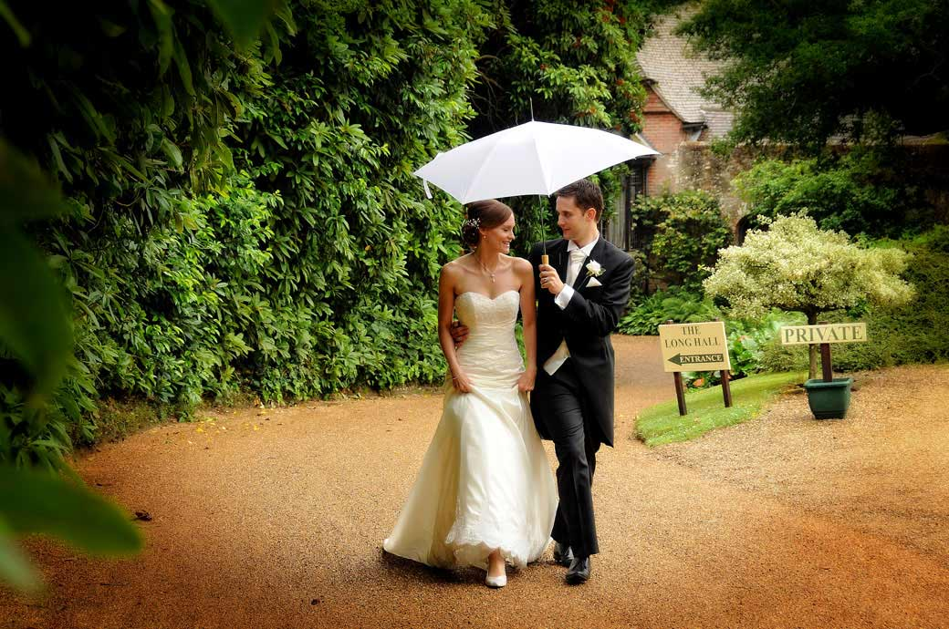 A romantic wedding photograph of the Groom protecting his wife from the rain under an umbrella on the drive at Ramster Hall Surrey wedding venue