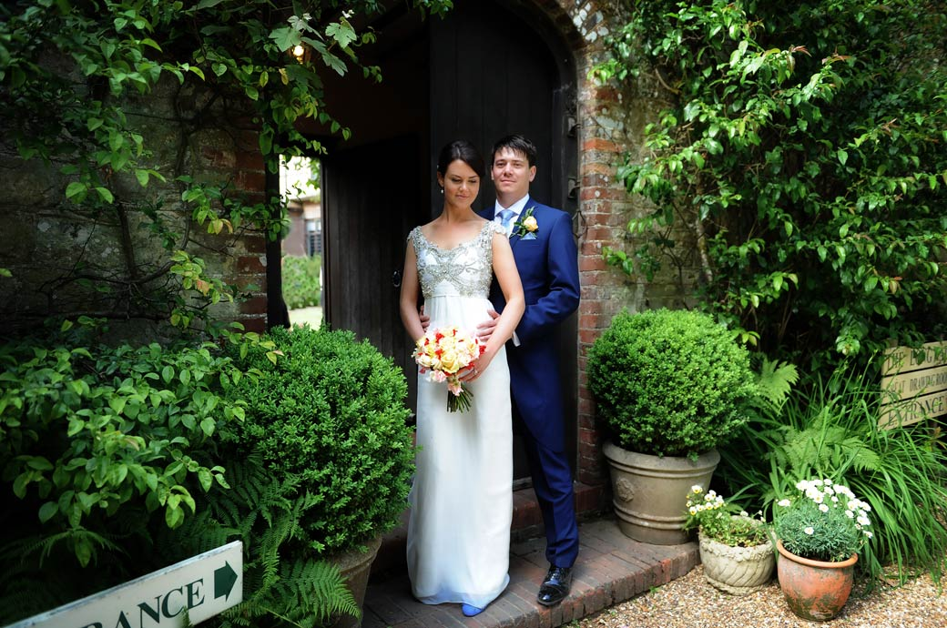 A proud Groom holds his pretty bride by her waist in the entrance to The Long Hall and Courtyard Garden at Surrey wedding venue Ramster Hall in Chiddingfold, Guildford