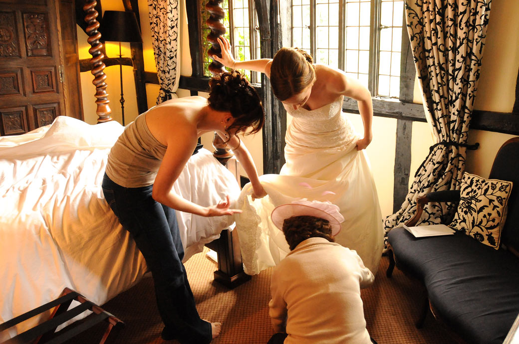 Bride being helped by her mother and bridesmaid in this getting ready wedding photo taken in the local pub in Chiddingfold before leaving for Surrey wedding venue Ramster Hall