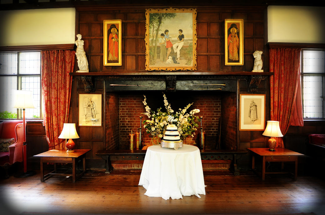 The wedding cake taking centre position in front of the fireplace in The Great Drawing Room at Ramster Hall an atmospheric wedding venue in Chiddingfold Surrey