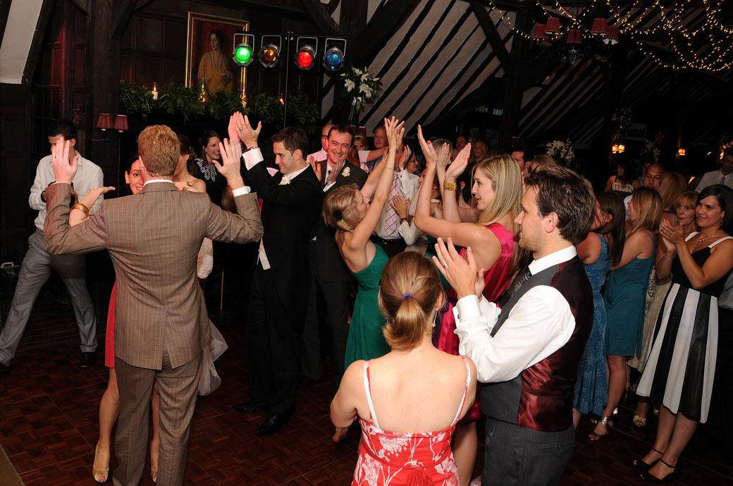 Guests captured clapping and raising their hands in the air in this fun photo taken in The Long Hall at a Ramster Hall wedding in Chiddingfold Surrey