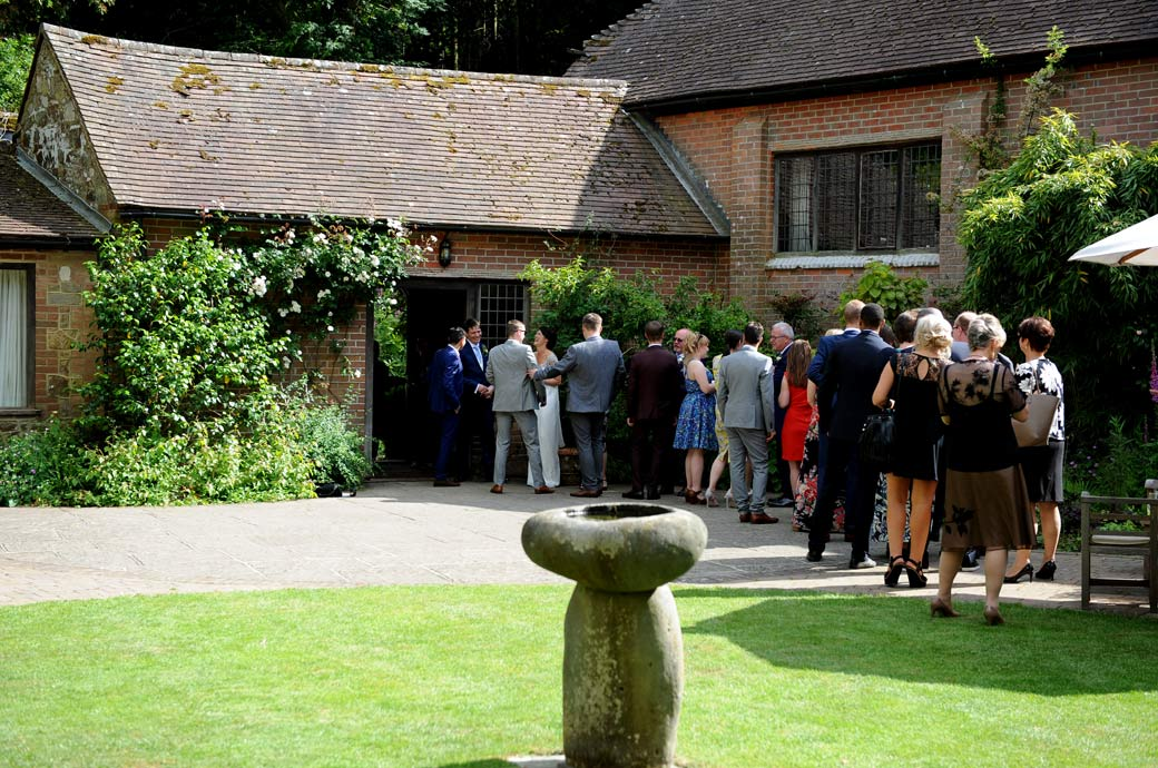 Guests captured in the wedding photo standing in line to be greeted and received by the newlyweds at Surrey wedding venue Ramster Hall before starting the wedding breakfast