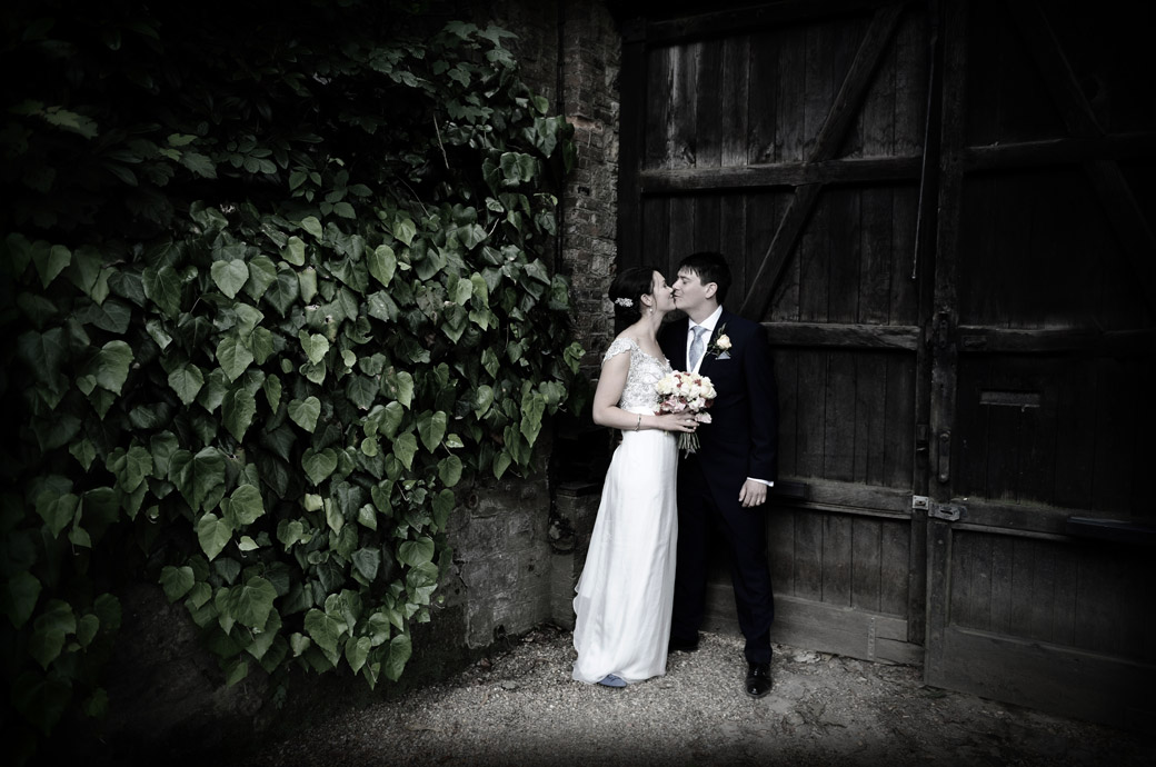 Newlyweds linger after a kiss in the beautiful grounds of the family owned Ramster Hall captured by Surrey Lane wedding photographers in the village of Chiddingfold