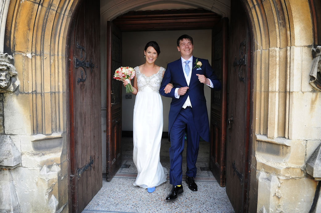 All smiles in this joyful wedding photo taken as the happy newlyweds exit Christ Church New Malden on their way to Ramster Hall a lovely Surrey wedding venue in Chiddingfold
