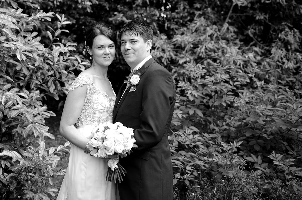 Wedding photograph of a handsome newlywed couple looking relaxed as they stand together amongst the shrubbery at Ramster Hall a wedding venue in Surrey