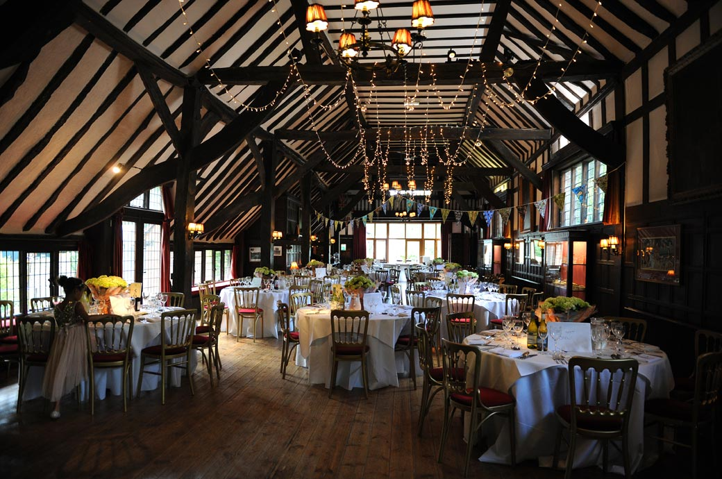 The wonderfully atmospheric Long Hall dressed and ready for the wedding breakfast and awaiting the entry of guests at the Surrey wedding venue Ramster Hall in Chiddingfold village