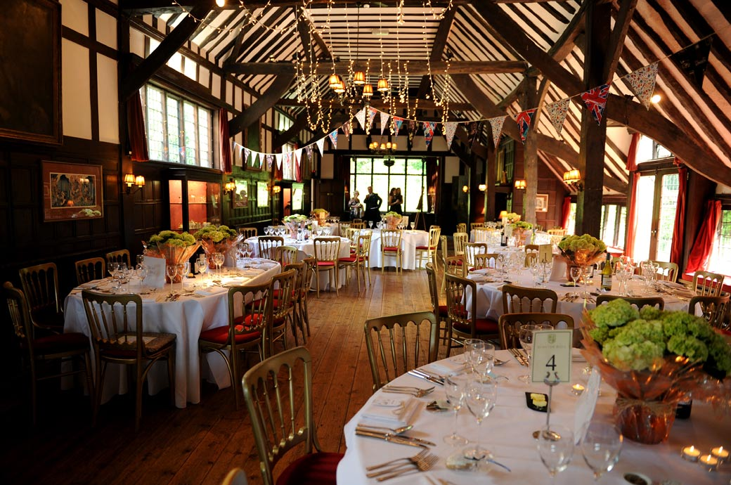 A classic wedding photograph of the atmospheric Long Hall dressed with fairy lights and bunting for the wedding breakfast at Ramster Hall in Chiddingfold Surrey