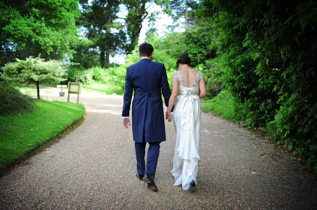 Hand in hand the newlywed couple walk up the drive for some more romantic wedding pictures at the delightful Surrey wedding venue in the village of Chiddingfold Ramster Hall