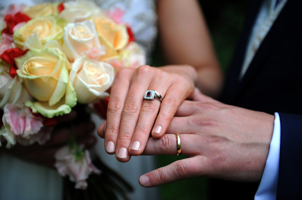Bride and groom's wedding rings on show alongside a colourful bouquet in this wedding photo taken in the luscious gardens at Ramster Hall in Chiddingfold Surrey near Guildford