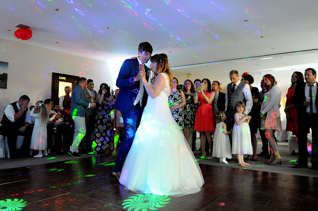 Wedding photograph of the newlywed couple enjoying their first dance in The Clarence Suite at Surrey wedding venue Reigate Hill Golf Club