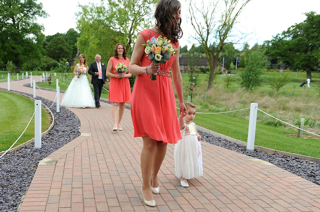 Lovely wedding picture of a Bridesmaid holding hands with a baby bridesmaid on the meandering Waterside path at Reigate Hill Golf Club in Gatton Bottom Surrey