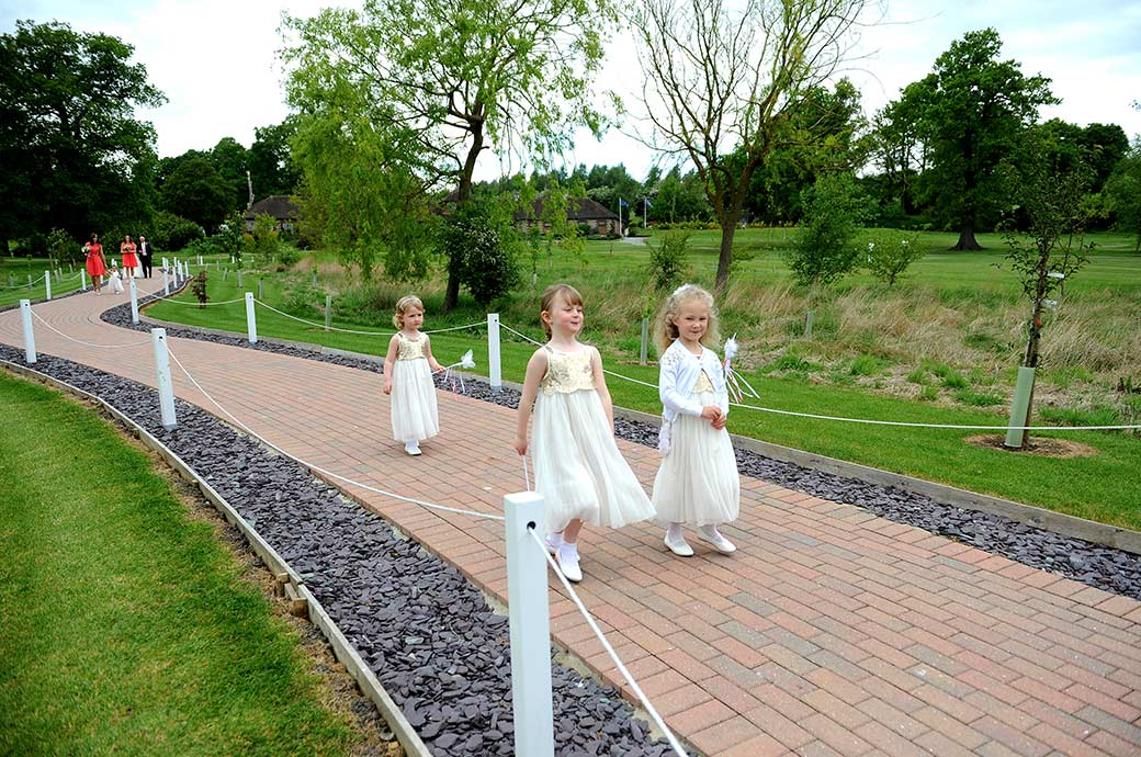 Three cute little bridesmaids at Surrey wedding venue Reigate Hill Golf Club dressed in white lead the wedding procession down the meandering path to the Waterside venue