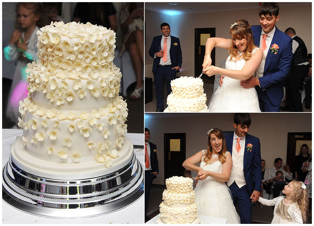 Happy newlywed couple have fun cutting their wedding cake in The Clarence Suite at Surrey wedding venue Reigate Hill Golf Club