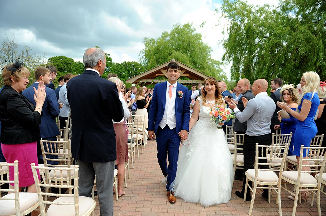 Young happy smiling couple walk hand in hand down the aisle of the outside Waterside venue in Surrey at Reigate Hill Golf Club to the applause of all the guests