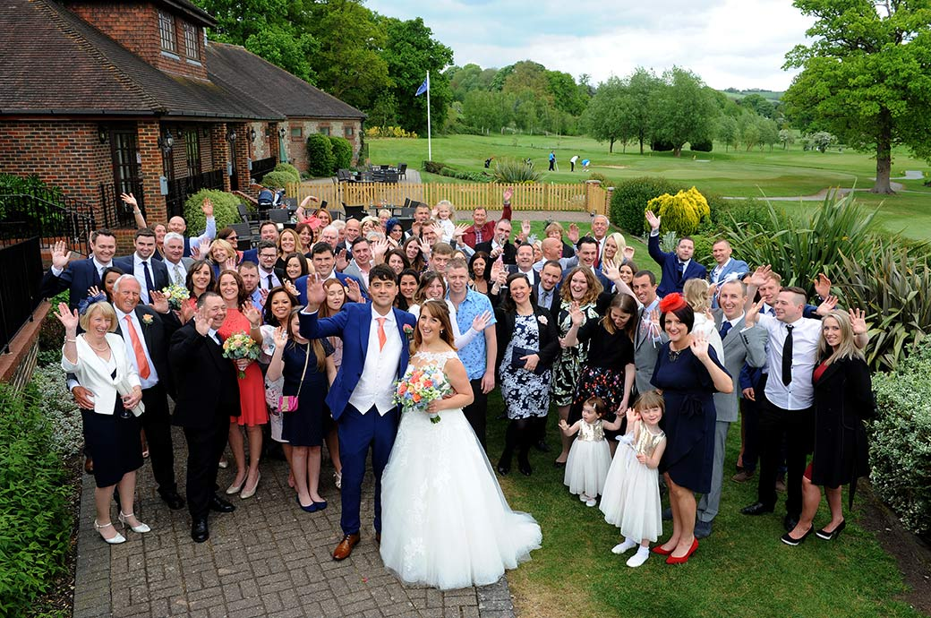 The popular everyone at the wedding waving photograph captured outside at Surrey wedding venue Reigate Hill Golf Club on the lawn and patio area
