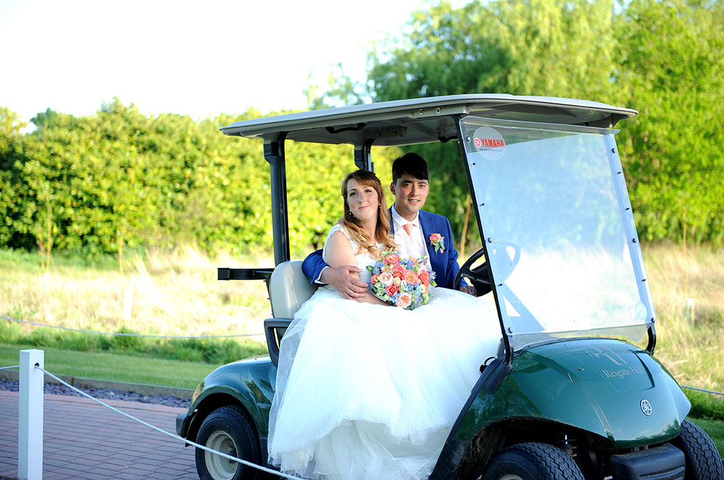 Content and happy smiling Bride and Groom at the green and tranquil Surrey wedding venue Reigate Hill Golf Club take a fun ride in a golf buggy