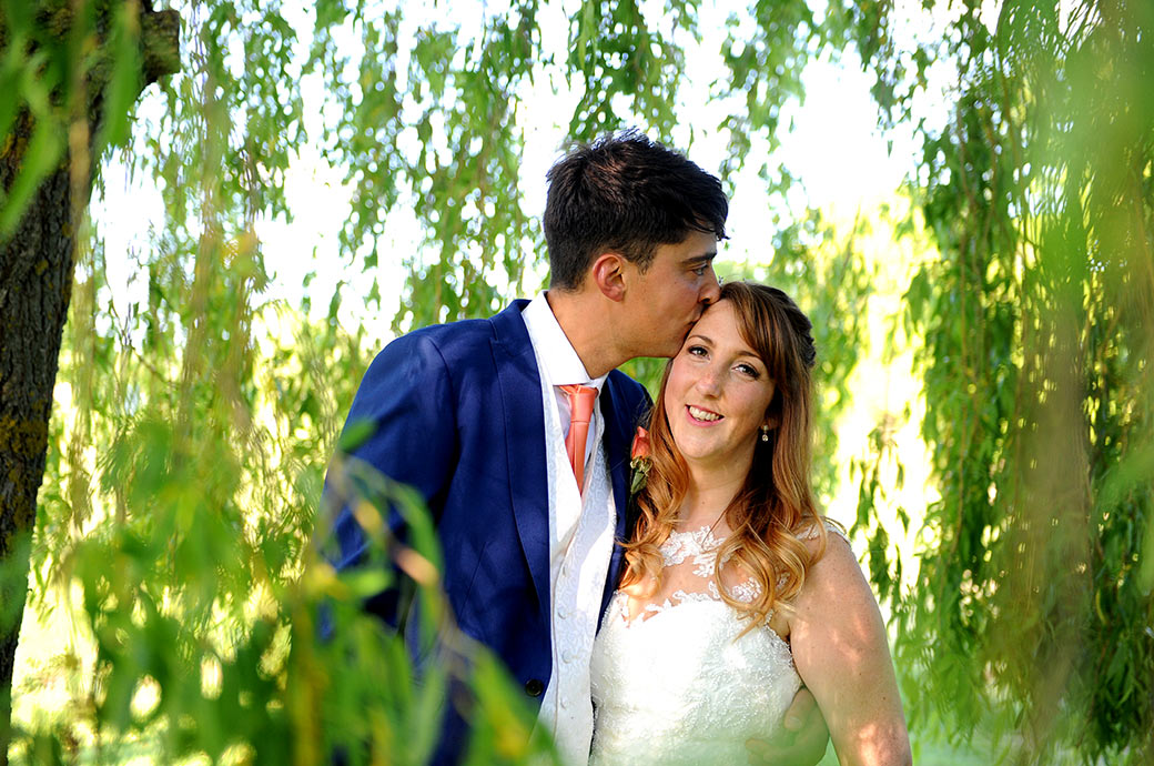 Relaxed smiling Bride at Reigate Hill Golf Club in Gatton Bottom Surrey receives a kiss from her Groom as they stand beneath a large willow tree
