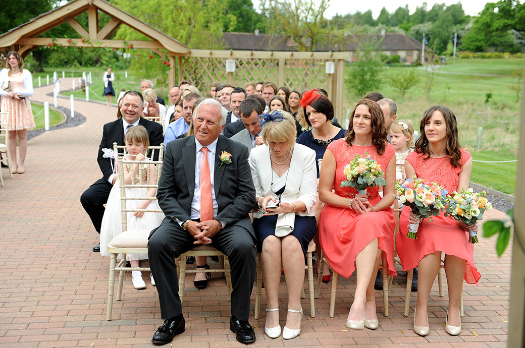 Close up of the front two rows of family and friends as they watch the Bride and groom during the wedding ceremony at Reigate Hill Golf Club Surrey in the outside Waterside venue