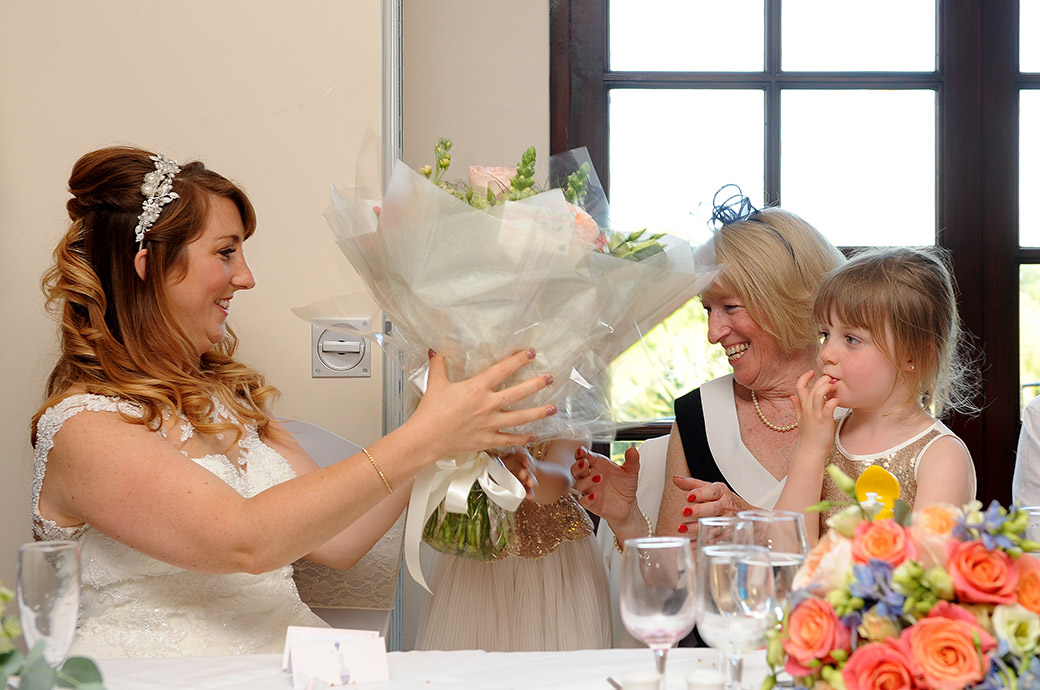 Bride presents a lovely flower bouquet to her mum on the head table in The Clarence Suite at Reigate Hill Golf Club relaxed and popular Surrey wedding venue
